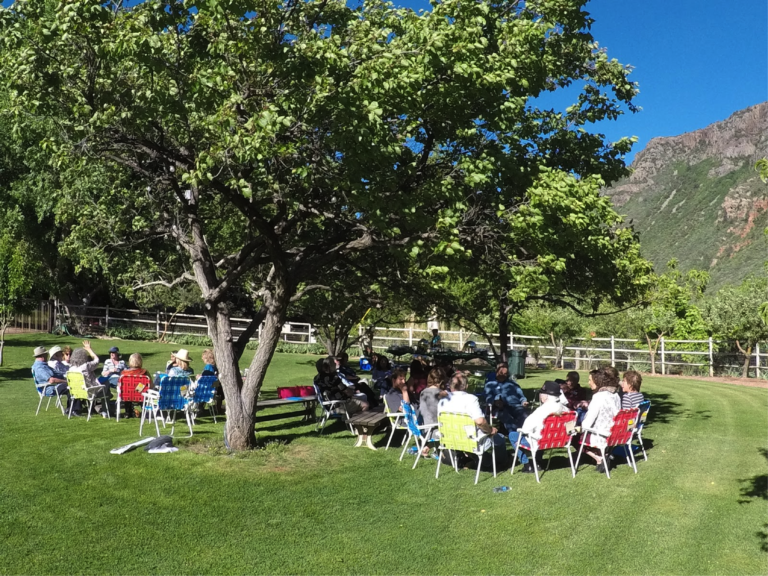 A group gathers in a beautiful setting to engage in collaborative dialogue, creating new ideas together.